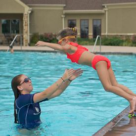 Child learning how to swim with Jeff Ellis Management lifeguard