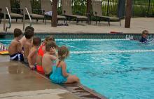 Children sitting on pools edge at Benders Landing Estates