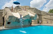Swimmer sliding down drop-off into plunge pool at Phillips Park Family Aquatic Center
