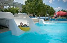 Child going down water slide in inner tube at Phillips Park Family Aquatic Center