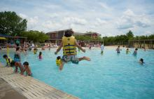 Child jumping in pool with lifejacket on at Splash Country Water Park
